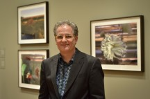 """Bruce Checefsky in front of his photoraphs in """"SuperNatural: Landscapes by Bruce Checefsky and Barry Underwood"""""""