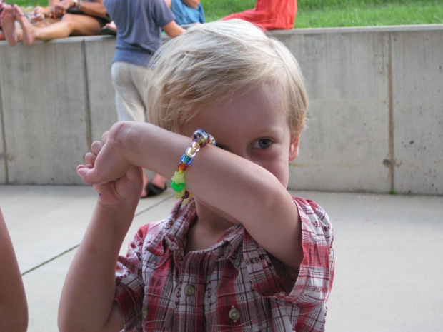 Showing off his plastic beads.
